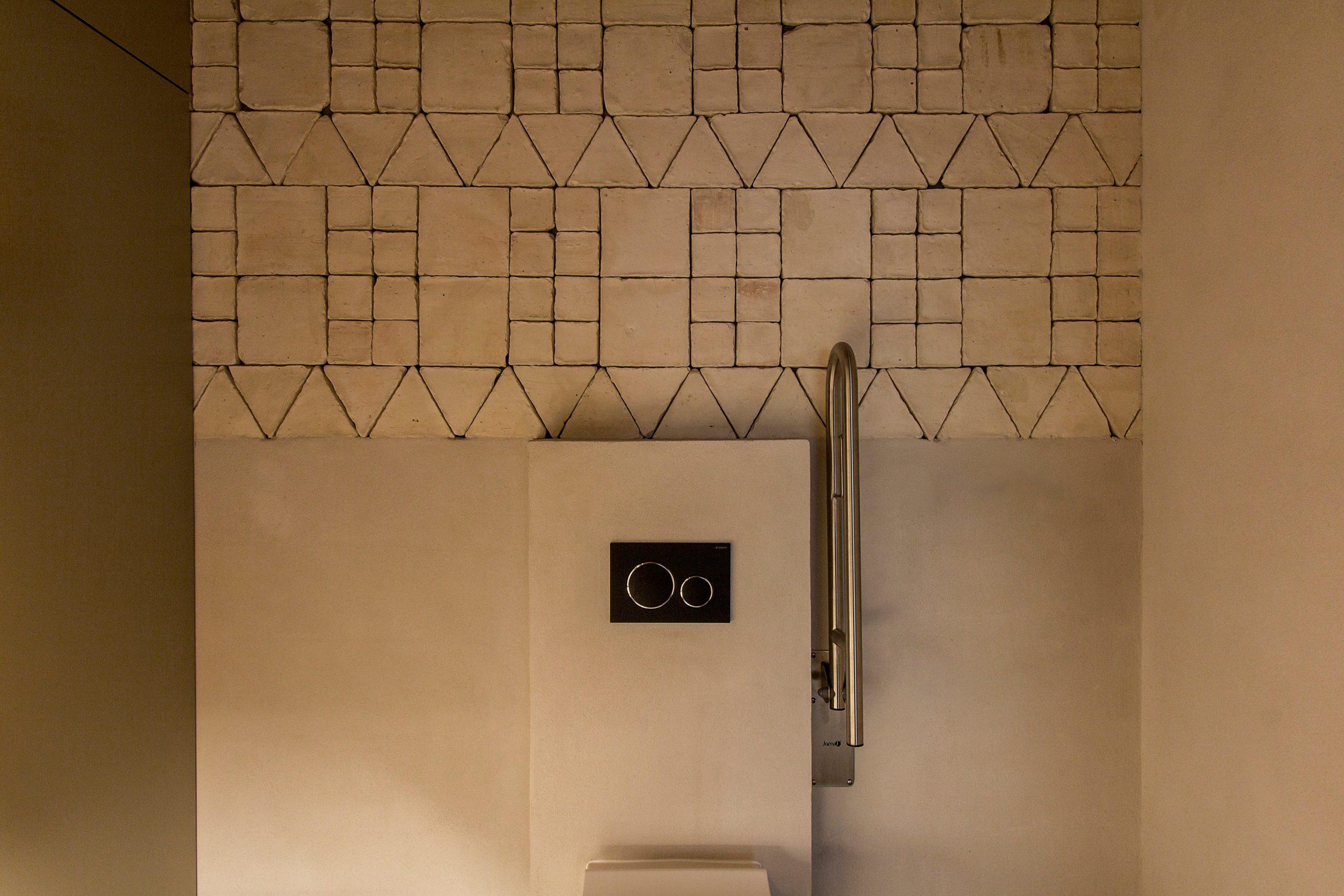 Detalle de pared compuesta por piezas de barro artesanales de Todobarro