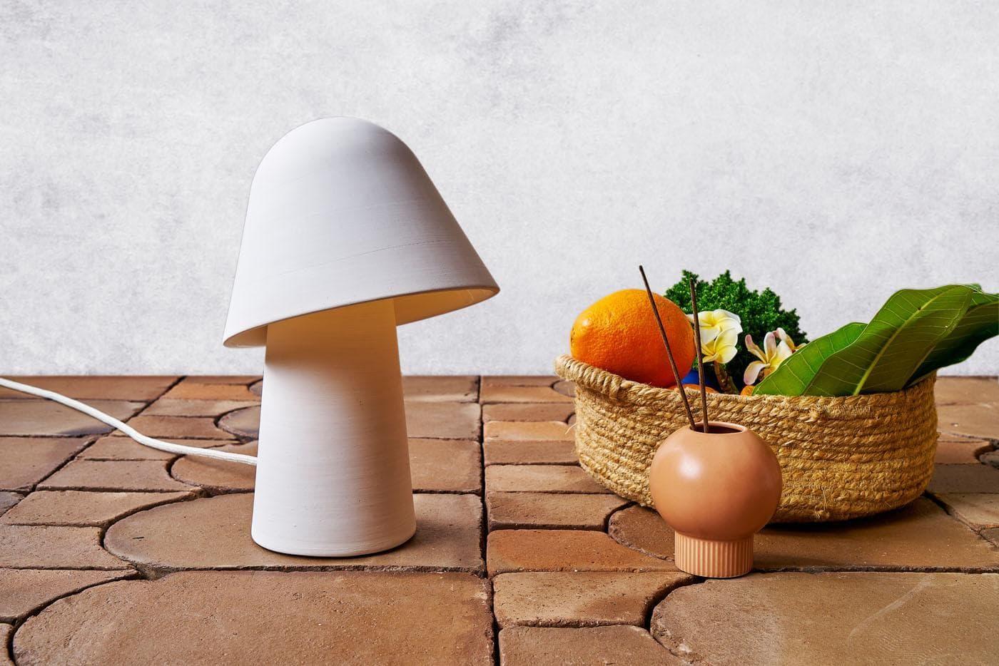 Lámpara y cesta de mimbre con frutas mediterráneas sobre baldosas de barro cocido artesanales