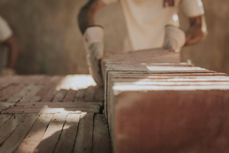 Maestro artesano colocando baldosas de barro cocido artesanales y ecológicas, un material que respeta los principios de la bioconstrucción