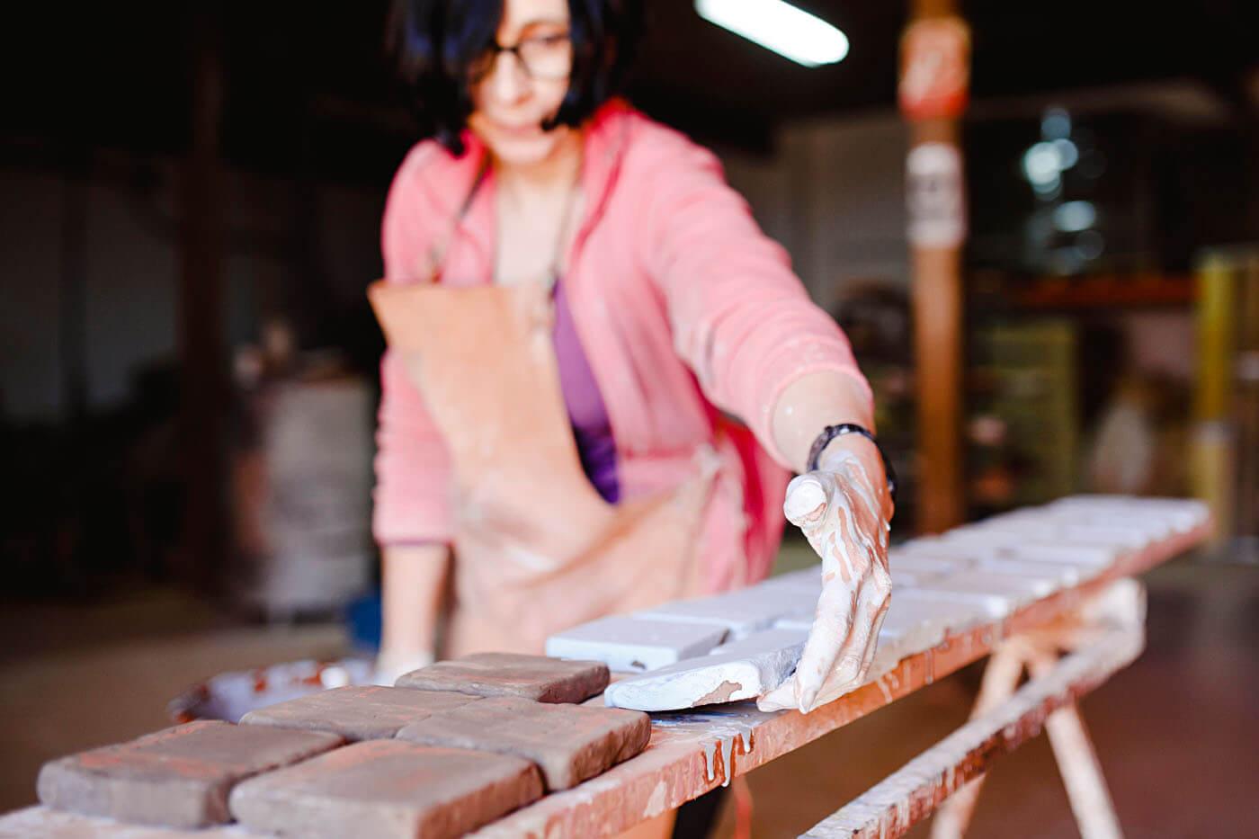 Neoartesania. Mujer trabajando con baldosas de barro cocido.