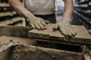 Neoartesanía. Plano de as manos de un hombre trabajando de manera artesanal el barro cocido desde una empresa sostenible