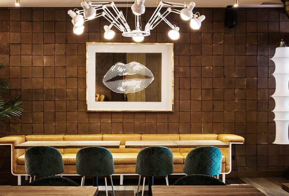 Fotografía de una de las paredes del restaurante cubierta con baldosas cuadradas de barro