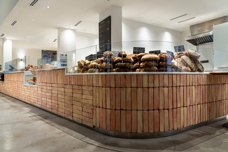 Expositor de pan en forma curva cubierto de ladrillos de barro rústicos en tonalidad salmón